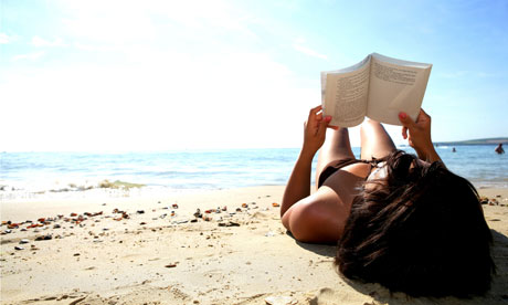 Woman reading a book on a beach