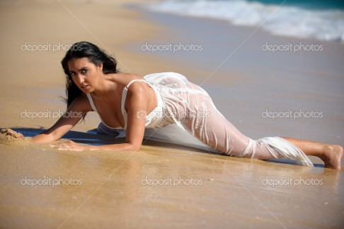 Brunette woman lying in the sand at the beach